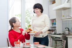 Зрелые женщины говоря на кухонном столе Стоковая Фотография RF