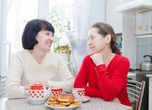 Зрелые женщины говоря на кухонном столе Стоковое фото RF