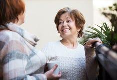 Зрелые женщины говоря на патио Стоковые Фото