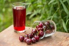 Зрелые красные вишни и стекло сока вишни на таблице в саде outdoors Стоковая Фотография RF
