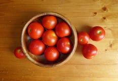 Зрелые красные томаты в шаре на деревянном столе Стоковые Изображения