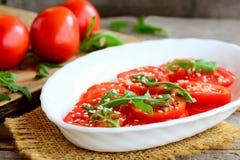 Зрелые куски томата, ракета arugula и салат семян сезама Салат томата сада на белой ткани плиты и мешковины Стоковая Фотография RF