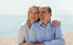 Зрелые пары вместе с пляжем моря в предпосылке Стоковые Изображения