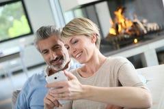 Зрелые пары используя smartphone Стоковая Фотография