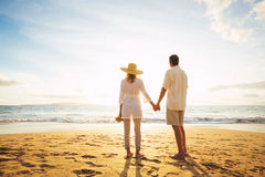 Зрелые пары идя на пляж на заходе солнца стоковая фотография