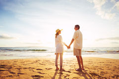 Зрелые пары идя на пляж на заходе солнца стоковое фото rf