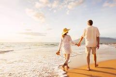 Зрелые пары идя на пляж на заходе солнца стоковое изображение rf
