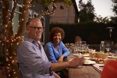 Зрелые пары наслаждаясь внешней едой в задворк стоковое фото