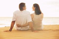 Зрелые пары наслаждаясь заходом солнца на пляже Стоковое Фото