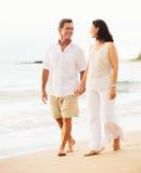 Зрелые пары наслаждаясь заходом солнца на пляже Стоковые Изображения RF
