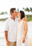 Зрелые пары наслаждаясь заходом солнца на пляже Стоковое Изображение RF