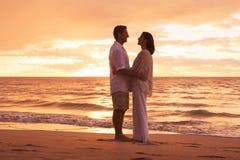 Зрелые пары наслаждаясь заходом солнца на пляже Стоковые Изображения