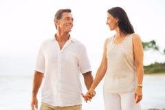 Зрелые пары наслаждаясь прогулкой на пляже стоковое изображение