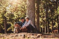 Зрелые пары под деревом с рюкзаками и компасом стоковое изображение