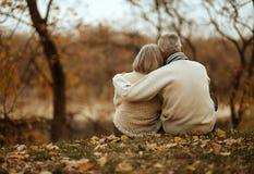 Зрелые пары сидя около озера Стоковая Фотография