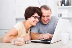 Зрелые пары смотря на компьтер-книжке дома стоковая фотография