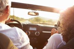 Зрелые пары управляя вдоль проселочной дороги в открытом верхнем автомобиле стоковые изображения rf