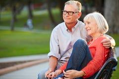 Зрелые романтичные пары сидя на скамейке в парке совместно Стоковые Фотографии RF