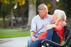 Зрелые романтичные пары сидя на скамейке в парке совместно Стоковая Фотография RF
