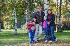 Зрелые родители с детьми стоят совместно в парке, во всю длину Стоковое Изображение RF