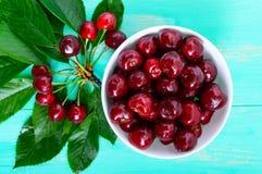 Зрелые сочные красные вишни в керамическом шаре на яркой деревянной предпосылке, среди листьев Стоковые Фотографии RF