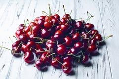 Зрелые сочные сладостные вишни на белом деревянном столе Стоковые Фотографии RF