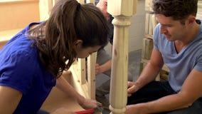 Зрелые студенты в классе плотничества работая на лестнице сток-видео