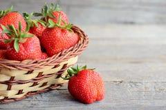 Зрелые сладостные плодоовощи клубник Большие красные клубники в плетеной корзине и на деревенской деревянной предпосылке с космос Стоковые Изображения