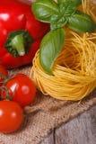 Зрелые томаты, высушенные макаронные изделия, свежий базилик и поднимающее вверх перца близкое Стоковое Изображение RF