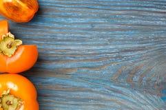 Зрелые хурмы на голубой деревенской деревянной доске с Стоковая Фотография