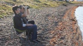 Зрелые любовники сидя на пляже и наслаждаться акции видеоматериалы