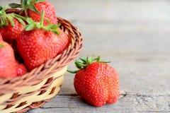 Зрелые яркие красные плодоовощи клубник Большие сочные клубники в плетеной корзине и на деревенской деревянной предпосылке с косм Стоковая Фотография