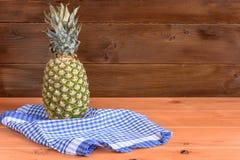 Зрелые anans кладут на голубое pololotentsa на деревянном столе и деревянной предпосылке Стоковые Изображения RF