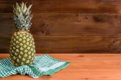 Зрелый ананас лежит на зеленом полотенце на деревянном столе и деревянной предпосылке Стоковое Изображение