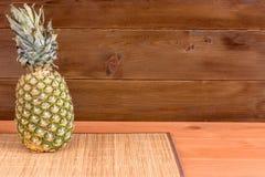 Зрелый ананас лежит на циновке на деревянном столе и деревянной предпосылке Стоковые Фото