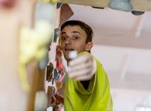 Зрелый альпинист получая владение на взбираясь стене Стоковая Фотография