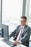 Зрелый бизнесмен работая на компьютере в офисе Стоковые Изображения RF