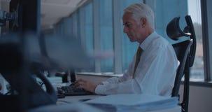 Зрелый бизнесмен работая на компьютере видеоматериал