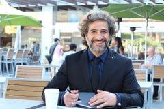 Зрелый бизнесмен работая на усмехаться кафа outdoors стоковое фото rf