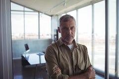 Зрелый бизнесмен стоя в офисе Стоковое Фото