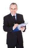 Зрелый бизнесмен с доской сзажимом для бумаги Стоковая Фотография