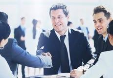 Зрелый бизнесмен тряся руки для того чтобы загерметизировать дело с его партнером и коллегами в современном офисе Стоковое фото RF