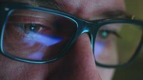 Зрелый взрослый человек с стеклами который работает на ноче Закройте вверх по съемке, отражениям видеоматериал
