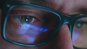 Зрелый взрослый человек с стеклами который работает на ноче Закройте вверх по съемке, отражениям акции видеоматериалы