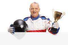 Зрелый гонщик автомобиля с золотым трофеем и шлем за панелью Стоковая Фотография