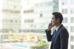 Зрелый и уверенно руководитель бизнеса смотря смотрящ из больших окон на взгляде города ниже Стоковая Фотография