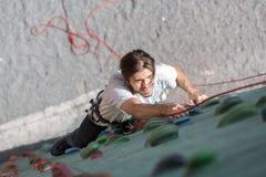 Зрелый мужской альпинист утеса на вертикальной стене Стоковое фото RF