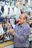 Зрелый мужской положительный приятный клиент покупая внешний кабель Стоковые Фото