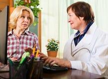 Зрелый доктор советуя с женским пациентом Стоковая Фотография RF