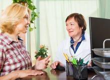 Зрелый доктор советуя с женским пациентом Стоковая Фотография